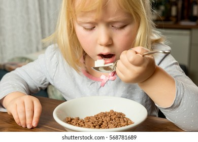 Young girl pretending to eat sugar lumps to illustrate the amount of added sugar in our breakfasts