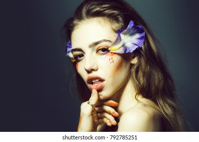 Young girl with pretty face and bright orange floral makeup with flowers blue petals in studio on grey background