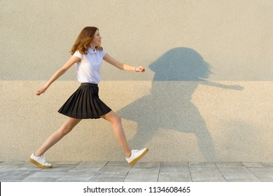 Young girl in the profile, walks along the gray wall, hurry, is late, takes big steps. Outdoor, copy space
