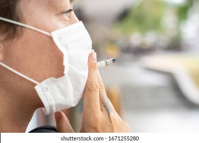 young girl protect herself with a mask against coronavirus and try to smoke