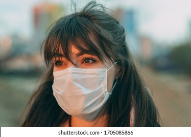 A young girl in a protective cries in the city on the street during sunset. COVID-19 pandemic. Coronavirus concept