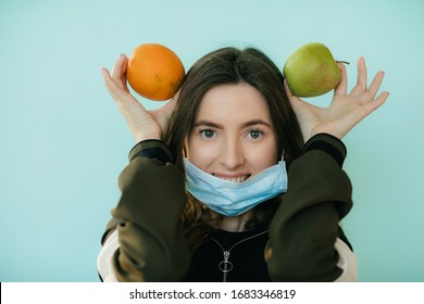 Young girl in a protective mask with fruits on a blue background. Healthy food in quarantine. COVID-19 Pandemic. Coronavirus concept.