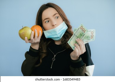 Young girl in a protective mask with fruits and dollars on a blue background. Healthy food in quarantine. Expensive food. COVID-19 Pandemic. Coronavirus concept.