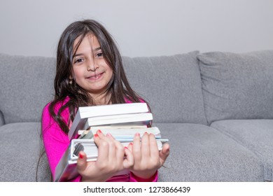 A young girl is proudly carying a pile of books