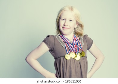 A young girl proudly showing off several gold medals that she is wearing around her neck.