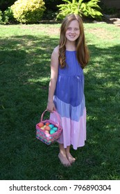 A young Girl in a Purple, Blue and Pink Dress holding a colorful Easter Basket full of Multi-Colored Easter Eggs standing on green grass