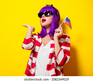 Young girl with purple hair holding United States flag on yellow background. Fourth July Holiday concept
