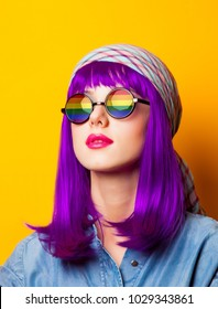 Young girl with purple hair and rainbow on suglasses on yellow background