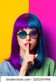 Young girl with purple hair and sunglasses on yellow background