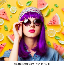 Young girl with purple hair and sunglasses on spring fruits background