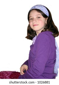 Young girl with purple hairband sitting isolated on white background