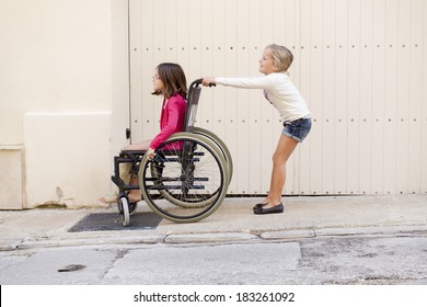 A young girl pushing her friend with a broken leg  in a wheelchair.