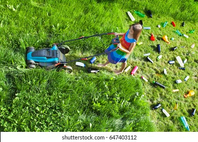 Young girl pushing a lawnmower cutting grass and leaving plastic litter behind - top view