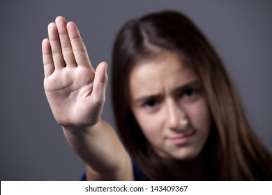 A young girl putting up her hand, to say no, or stop, with a serious frowned expression.