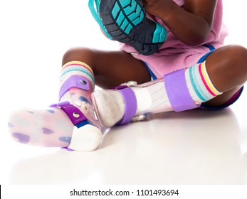 Young girl putting on her AFO braces