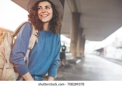 Young girl at the railway station waiting for the departure of train with backpack