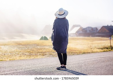 Young girl in a raincoat in the morning at dawn against a background of fog and mountains.