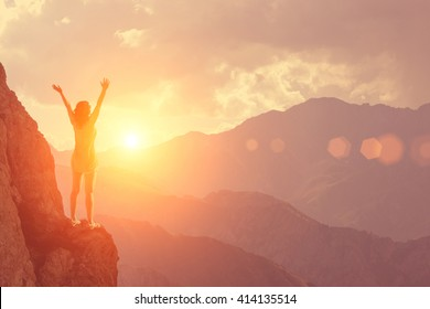 The young girl raised her arms up to the sun on a background of mountains and sky with clouds