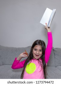 A young girl is raising her book to celebrate completion of he homework
