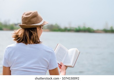 Young girl reading a book by the lake. View from back.