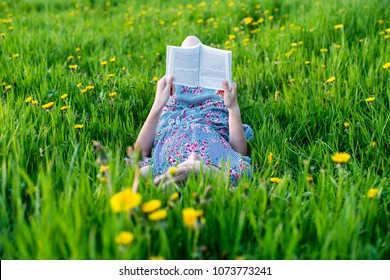 Young girl reading a book in field of grass