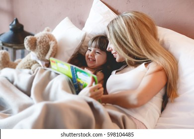 Young girl reading a book with her mother. Portrait of cute girl listening to her mother telling an interesting story at home. fairytale at home, bedtime, childhood and family concept