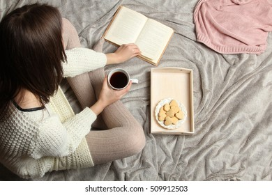 Young girl reading a book on the bed. Top view