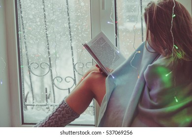 Young girl reading a book on the window. She wrapped herself in a blanket. Window with garland.