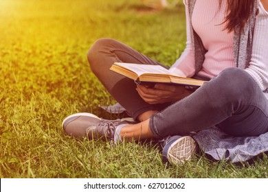 Young girl reading book outside sitting on green grass in park on meadow. Read and rest