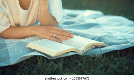 Young girl reading a book in the park