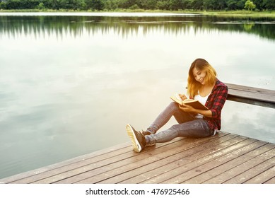Young girl reading book and sitting on wood balcony by river