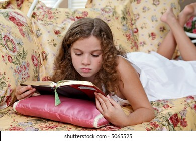 A young girl reading her Bible while lying on her bed.