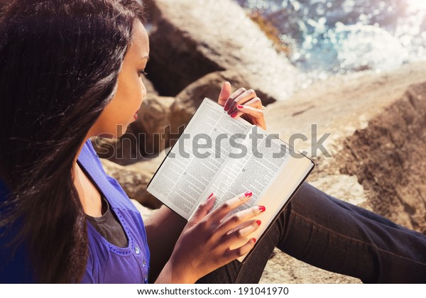 Young girl reading her Bible by the sea