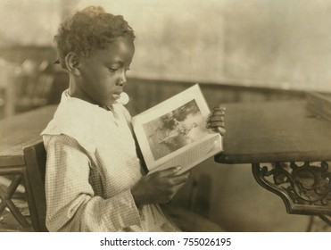 Young girl reading an illustrated book in Pleasant Green School, near Marlinton, West Virginia. The one-room school was one of the best schools for African Americans in Pocahontas County. Oct. 1921. P