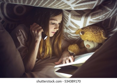 young girl reading a magic book in the dark holding a flashlight in hand under a blanket with a toy teddy bear