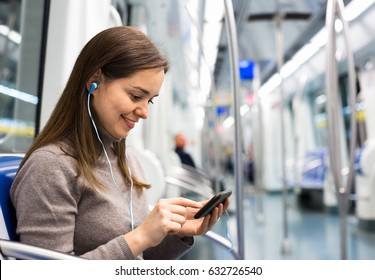 Young girl reading from mobile phone screen in metro