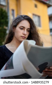 Young girl reading a newspaper outdoors .Yellow house in background