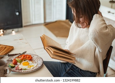 young girl is reading an old book at breakfast. Close-up hands and dinner table setting. Country style. Scrambled eggs and fresh vegetables and reading an interesting book in the morning