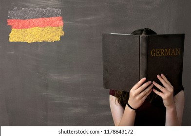 A young girl reading and studying a German text book sitting in front of a chalkboard with a German flag drawn in coloured chalk in the top left corner of the black board.