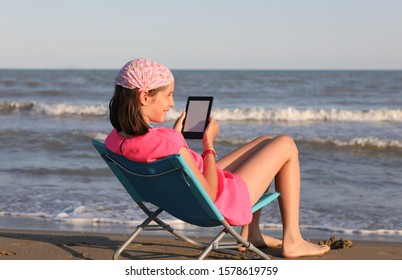 young girl reads her ebook by the sea in summer