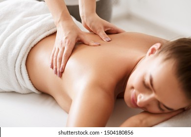 Young girl receiving back massage with closed eyes in spa center, closeup