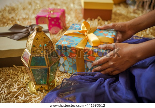 A young  girl receiving a gift. Eid celebration -a happiest moment for a kids. Stock photo.