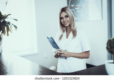 Young Girl at Reception of Modern Beauty Clinic. Modern Cosmetology. Proffesional Cosmetologist. Woman in White Uniform. Girl in White Coat. Smiling Woman. Worker with Tablet in Hands.