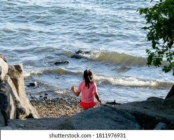 A young girl in a red bathing suit and red and white striped shirt enjoys a small public pebble beach on Lake Washington.