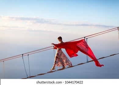 Young girl with red cloth goes on the suspension bridge