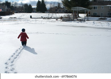 Young girl in a red coat and blue hat leaves a trail of footprints as she walks through a field of snow to houses in the background