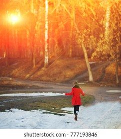 Young girl in a red coat flees, waving his arms, on a snowy road in the Park