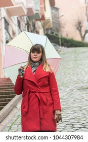 A young girl in a red coat walks under an umbrella in the Balat district of Istanbul. In the background beautiful houses pastel colors.