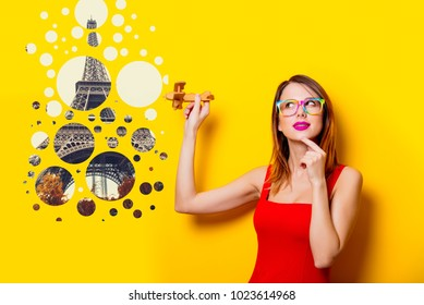 Young girl in red dress with airplane toy dreaming about travel to Paris on yellow background