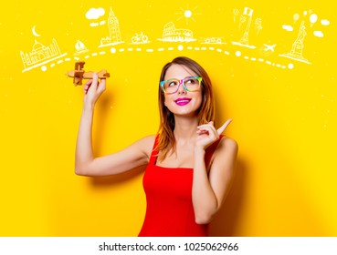 Young girl in red dress with airplane toy dreaming about world attractions on yellow background